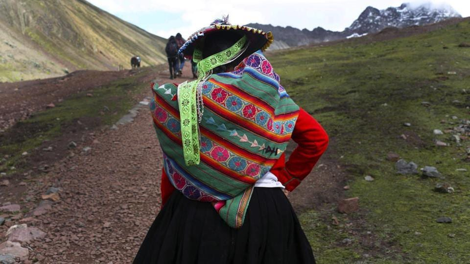 An Andean woman walks up to the mountain. Despite all the challenges, roughly 500 villagers have returned in the last couple of years to take up their ancestral trade of transporting goods across the Andes. The difference is that now they are hauling tourists on horseback. (Martin Mejia / AP)