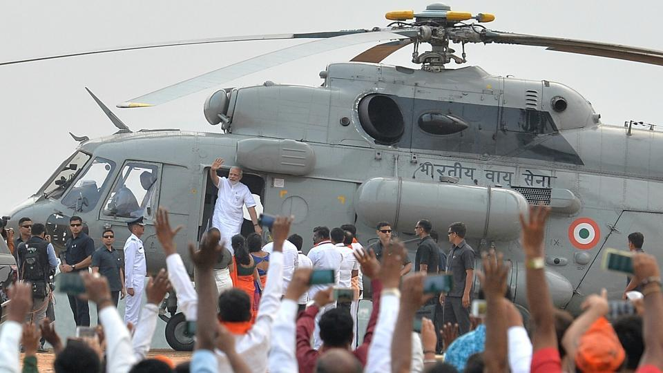 Prime Minister Narendra Modi greets BJP supporters after landing in an Indian Air Force helicopter at an election campaign rally in Bangalore, Karnataka on May 3, 2018. (Manjunath Kiran / AFP)