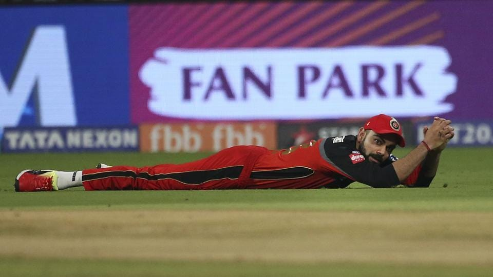 Royal Challengers Bangalore captain Virat Kohli falls after an unsuccessful fielding attempt to catch of Kolkata Knight Riders' Sunil Narine during the VIVO IPL Twenty20 cricket match in Bangalore, Karnataka on April 29, 2018. (Aijaz Rahi / AP)