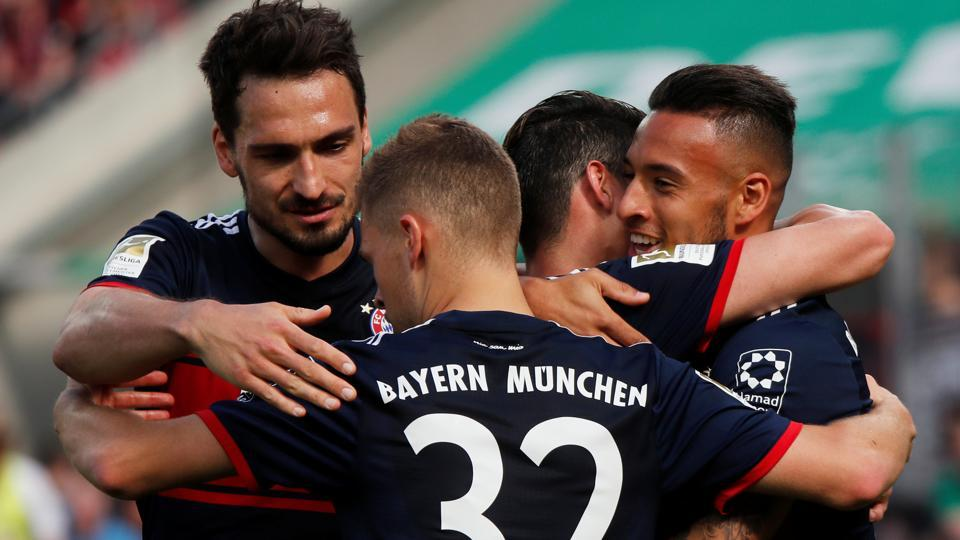 Bayern Munich's Corentin Tolisso celebrates with team mates after scoring their third goal against FCCologne.