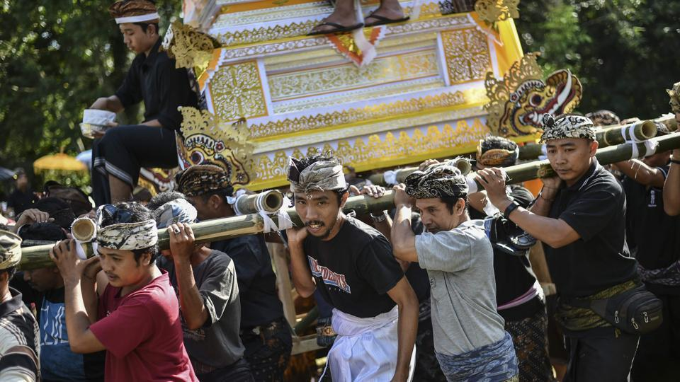 Family members and villagers transport the bodies of the deceased, placed into a 'wadah', or portable shrine, in a procession. The coffins are paraded through town so people can say goodbye, and also rotating thrice at every  major intersection to confuse evil spirits that might want to disturb the solemn ceremony. (Bay Ismoyo / AFP)