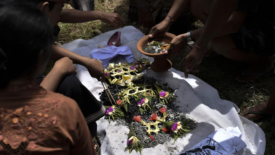 Following the blaze, the ashes are spread on a large piece of fabric dressed with flowers. Villagers in traditional sarongs march to a river where the remains are released into the gurgling water. (Bay Ismoyo / AFP)