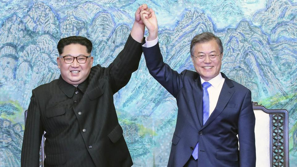North Korean leader Kim Jong Un (left) and South Korean President Moon Jae-in raising their hands after signing a joint statement at the border village of Panmunjom in the Demilitarized Zone, South Korea.