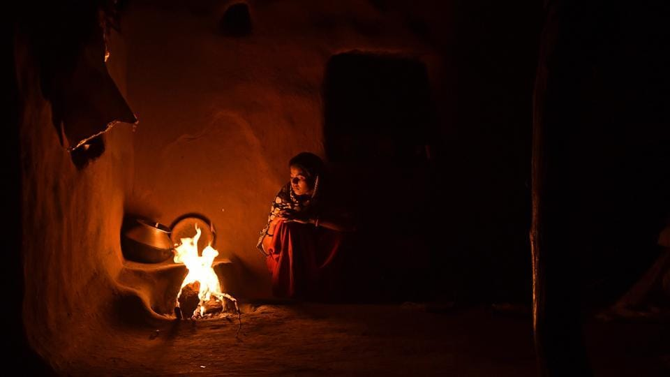 A woman cooks food by fire, the only light inside her home in Kraska village. The government has been trying to relocate Kraska and other villages under the CTH area in order to create an inviolate region free from human presence that can allow the reintroduction of tigers in Sariska for a number of years now. (Anindito Mukherjee / Bloomberg)