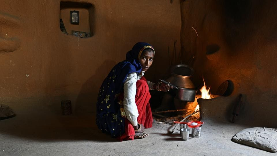 A woman cooks in her home in Kraska village. While a few villages have opted for the government's relocation package of ₹10 lakh to every adult member of the family, resulting in the creation of sanctuaries for female tigers ST-3 and ST-5 and their progeny around Bhagani village, the majority have stayed on stalling the efforts. (Anindito Mukherjee / Bloomberg)