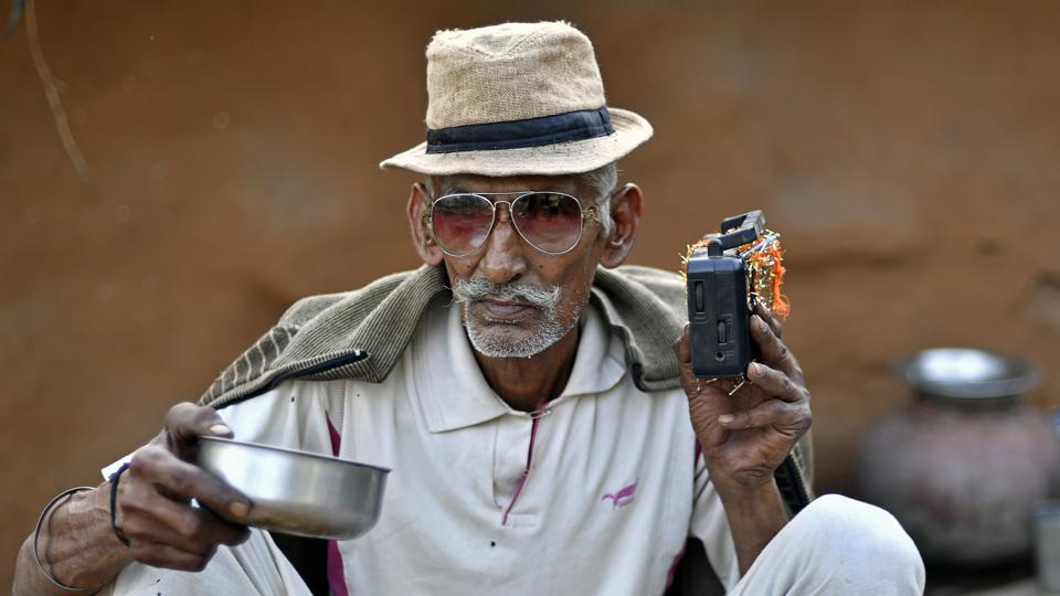 A man listens to a battery powered radio at a home in Kraska village. Some families don't want to leave their homes and others are sticking it out in hope of a better deal. Authorities don't intend to provide or maintain utility services to these areas. (Anindito Mukherjee / Bloomberg)