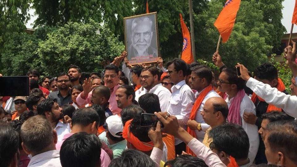 Hindu Jagran Manch activists hold a portrait of Raja Mahendra Pratap Singh, demanding its installation at AMU in Aligarh on Sunday.