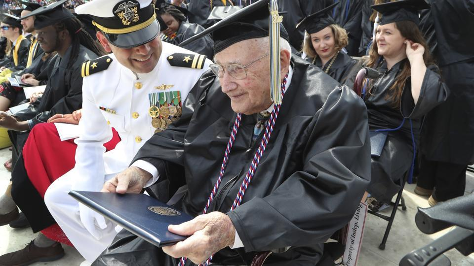 World War II veteran Bob Barger, assisted by Haraz Ghanbari, University of Toledo director of military and veteran affairs, left, smiles after receiving his diploma at the commencement ceremony at the university, Saturday, May 5, 2018, in Toledo, Ohio.