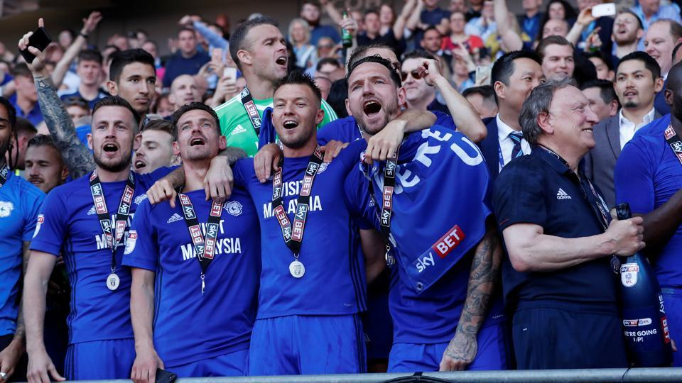 Cardiff City manager Neil Warnock, Sol Bamba, Gary Madine and team mates with the trophy as they celebrate promotion to the Premier League.