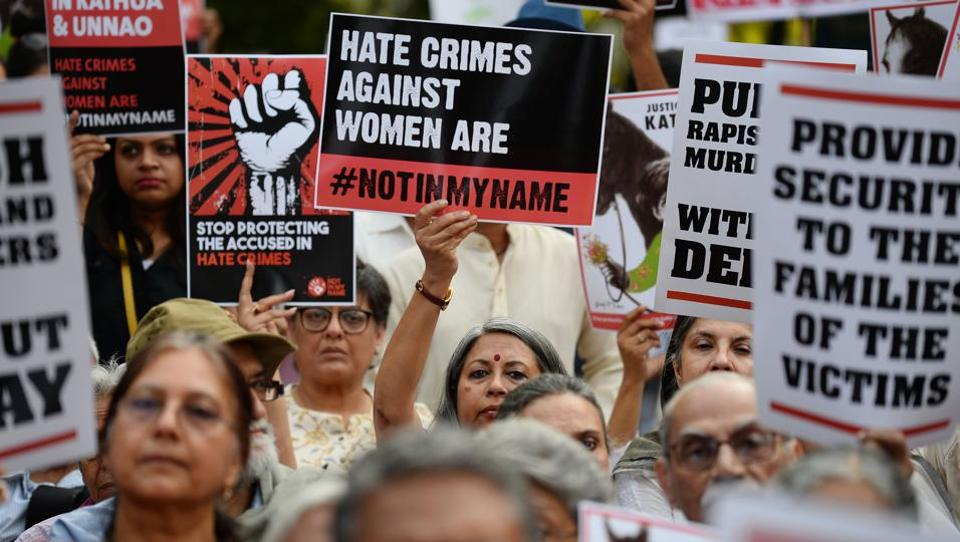 In this file photo taken on April 15, 2018, demonstrators hold placards during a protest against rape, in New Delhi.
