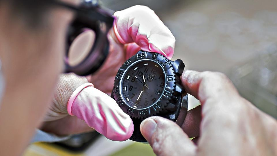 A watchmaker examines his creation.