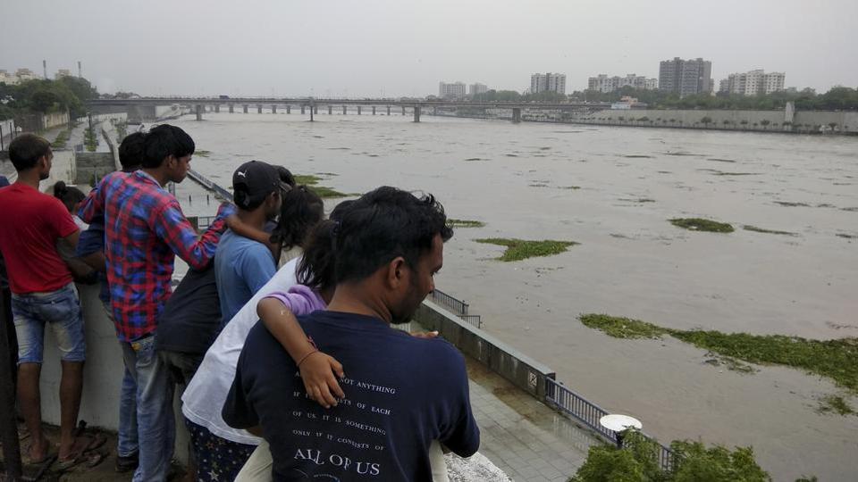 People look at a flooded River Sabarmati in Ahmadabad.