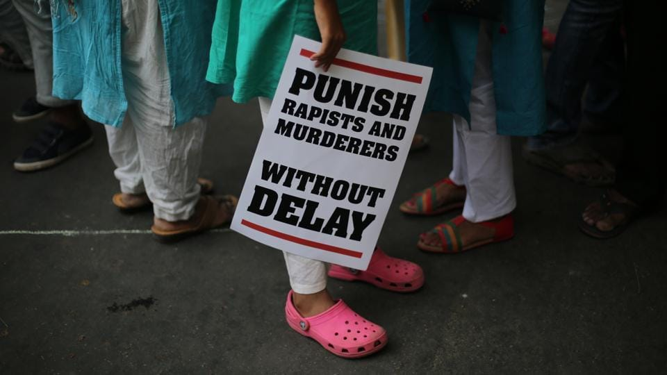 In this April 15 file photo, a protestor stands with a placard during a protest against rape, in New Delhi.