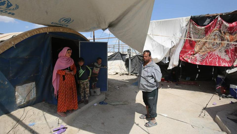 Displaced Iraqis stand outside a tent where they are taking shelter in a camp for internally displaced people near al-Khalidiyeh in Iraq's western Anbar province on April 24, 2018.