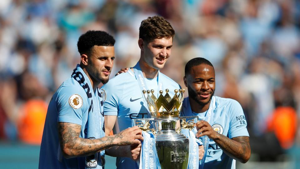 Manchester City's John Stones, Kyle Walker and Raheem Sterling pose as they celebrate with the trophy. (REUTERS)