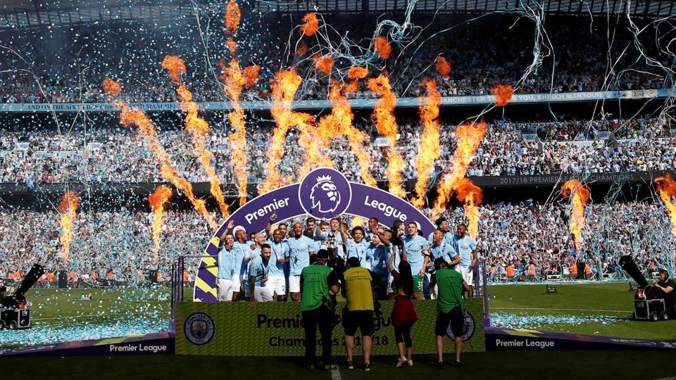 Manchester City celebrate with the trophy on Sunday. (REUTERS)