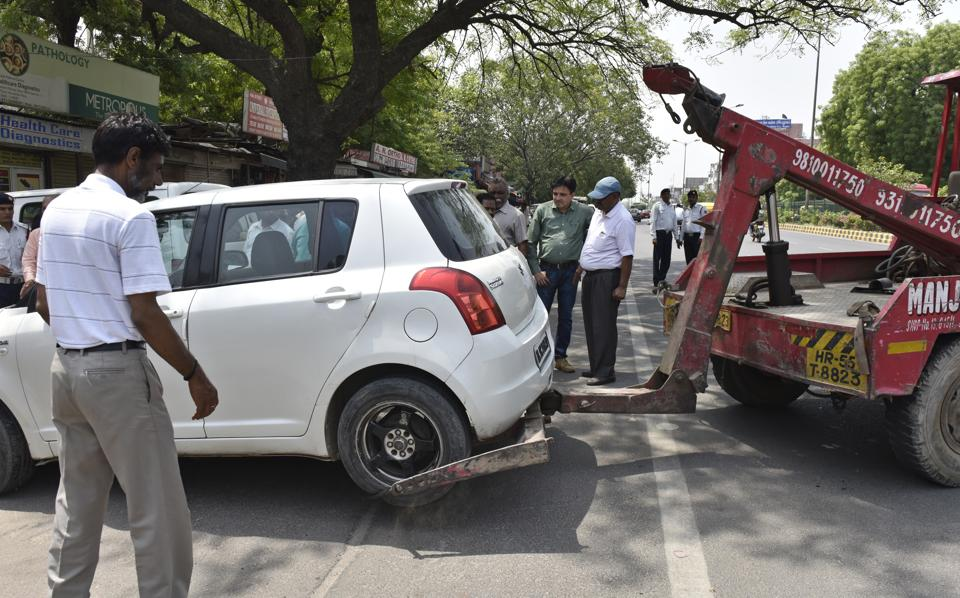Municipal and police officials tow away a car from no-parking zone in Yusuf Sarai in south Delhi on May 05, 2018.