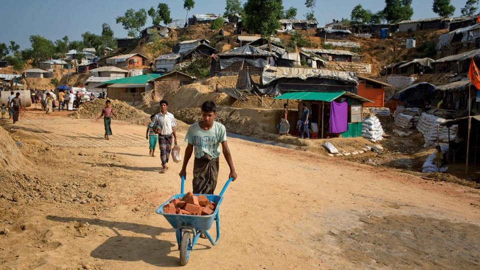 A Rohingya refugee carries bricks to rebuild his makeshift house, in preparation for the approaching monsoon season at the Kutupalong Rohingya refugee camp in Bangladesh.