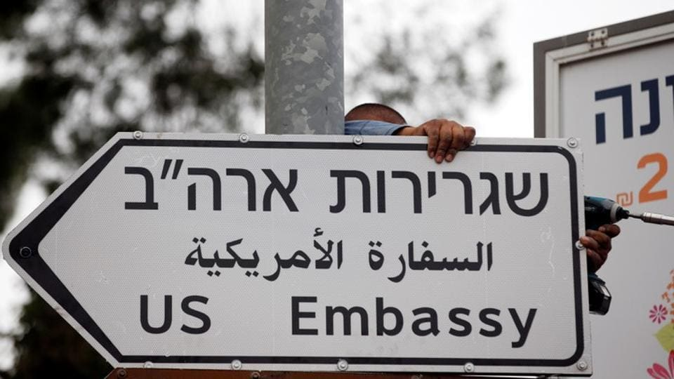 A worker hangs a road sign directing to the US embassy, in the area of the US consulate in Jerusalem, May 7, 2018.