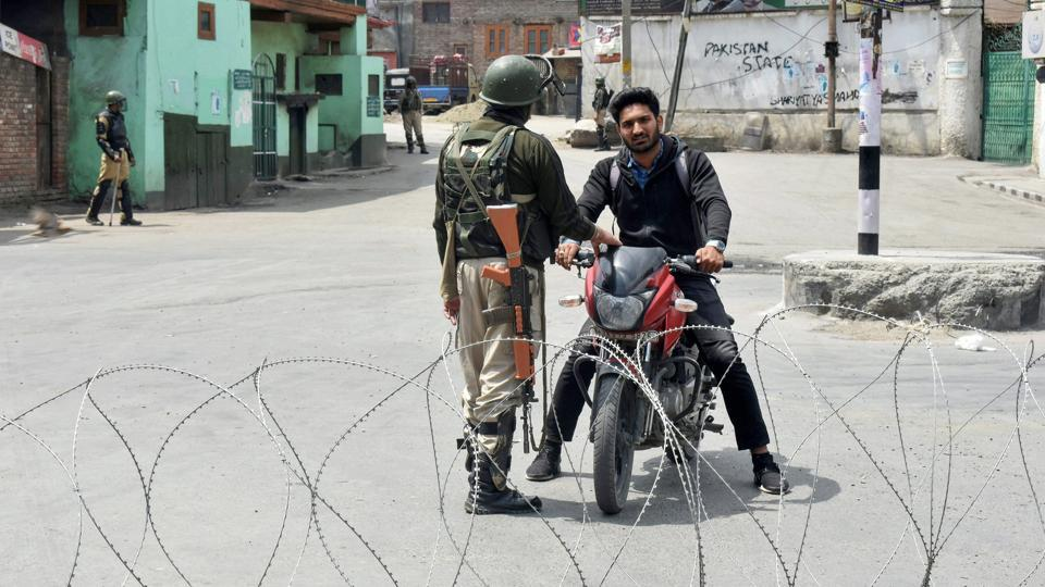 A security personnel stops a bike rider during curfew-like restrictions imposed to maintain law and order in Srinagar on Sunday.