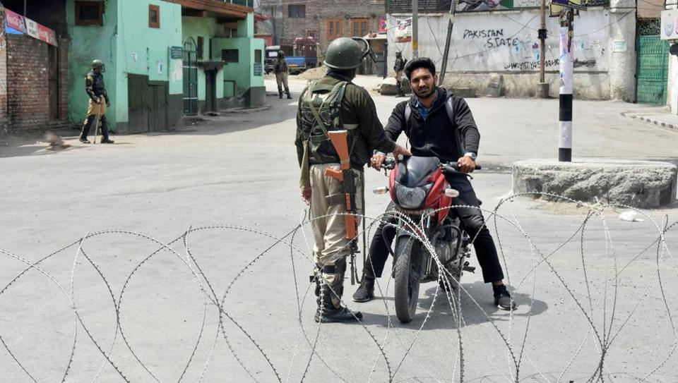 Security personnel stop a bike rider during curfew-like restrictions imposed to maintain law and order in Srinagar on Sunday. The authorities have put up barricades as well as concertina wires across the city in view of a protest march called by separatists.
