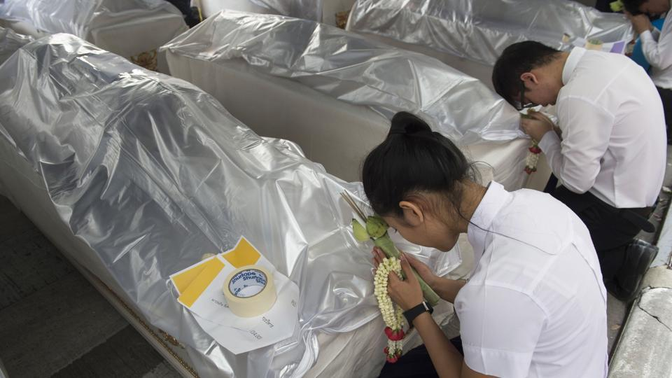 As a Brahmin priest recited prayers, the second-year students held jasmine garlands and prayed over their anatomy aides, whose remains were wreathed in plastic.  (Romeo Gacad / AFP)