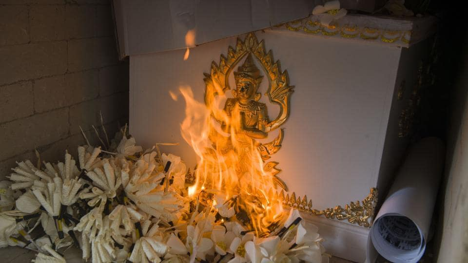 Flowers lit by a flame from the Thai Royal family burns the ceremonial bier bearing cadavers. (Romeo Gacad / AFP)