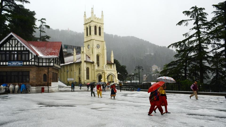 People take a stroll with umbrellas at Ridge as Shimla received hailstorm on Tuesday. Shimla and its surrounding areas were lashed by a severe hailstorm, throwing normal life out of gear. (Deepak Sansta/HT)