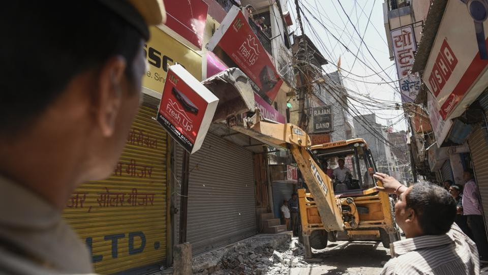 South Delhi Municipal Corporation (SDMC) officials demolish encroachments during an anti-encroachment drive at a market in Kotla Mubarakpur in New Delhi on Tuesday. (Burhaan Kinu / HT Photo)