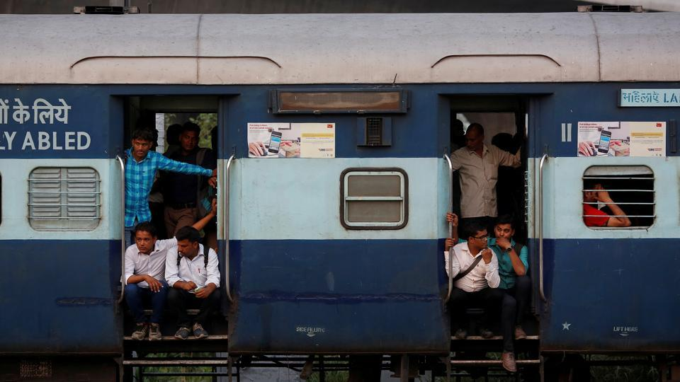 Commuters sit on the doorstep of a moving train in New Delhi.