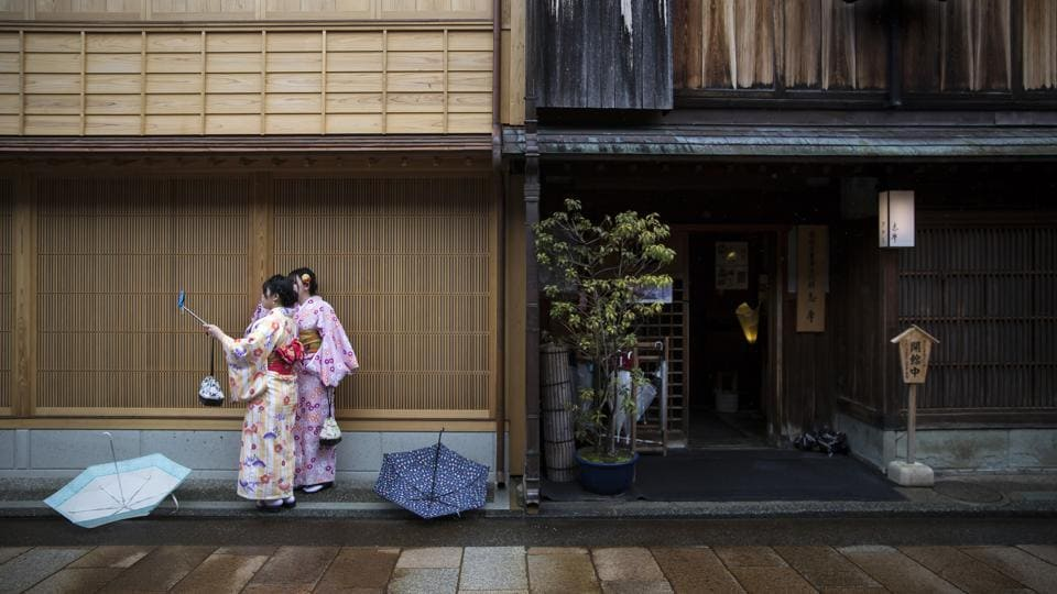 "Tourists wearing rental kimonos take pictures in the Higashi Chaya district of Kanazawa, Japan.""My mother told me the kimono business is risky and volatile,"" Ochi said, adding that her mother's shop struggled after the bubble economy ended in the early 1990s. But now, she said, business was booming and she expects the Tokyo 2020 Olympic Games will drive new demand as tourists flock to Japan. (Tomohiro Ohsumi / Bloomberg)"