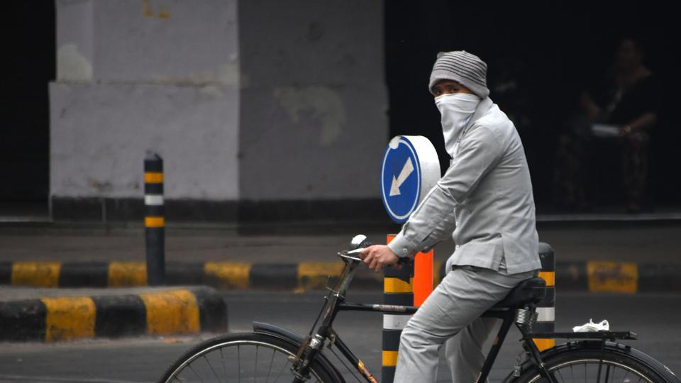 A man wears face protection against air pollution while riding on  a bicycle in New Delhi.