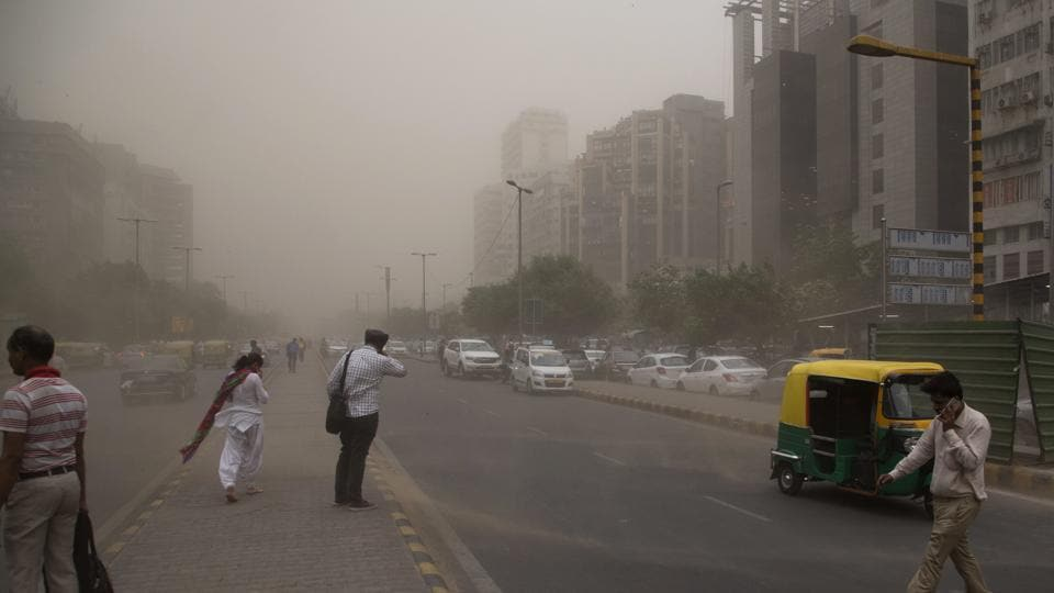 In this May 2 photo, people cross a road, enveloped by dust rising from a storm in New Delhi,