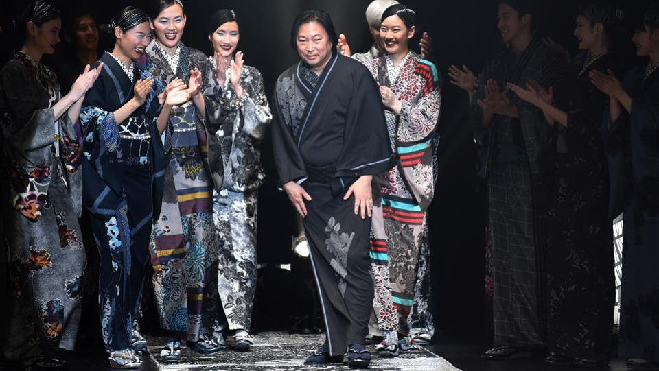 "Jotaro Saito (C) greets the audience at the end of the Tokyo Fashion Week. ""What's fabulous, what's unfashionable and what's cool change every year. It's wrong that kimonos don't change even if everything else is changing,"" said the Kyoto-based designer, whose work has been worn by American singer Lady Gaga. ""Kimonos are not something old. Wearing a kimono is the coolest and the most fun thing,"" he added. (Kazuhiro Nogi / AFP)"