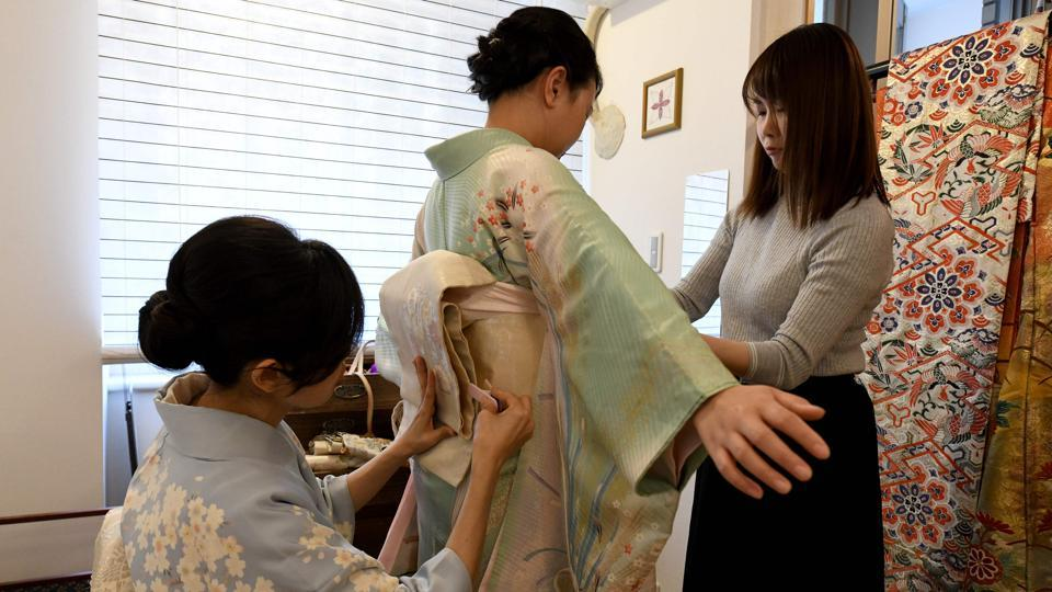 "And while demand is falling among the Japanese, services renting kimonos to foreign visitors are booming. ""Kimono is a piece of Japanese culture. I really wanted to experience that,"" said  Ruby Francisco (C), a Dutch tourist who rented a pale green kimono at Kahori Ochi's (L) shop. A kimono outfit starts with an undergarment known as a nagajuban, over which the kimono is layered, held in place with a thick obi belt and string. (Kazuhiro Nogi / AFP)"