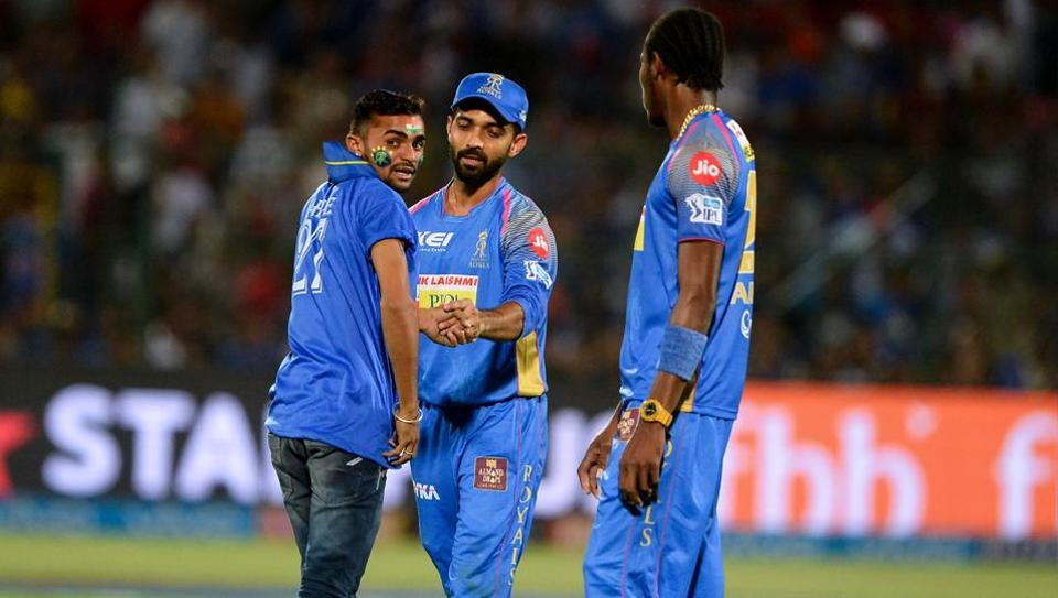 A fan of Rajasthan Royals team captain Ajinkya Rahane (C) enters the pitch to take a selfie picture during the 2018 Indian Premier League (IPL 2018) match between Rajasthan Royals and Kings XI Punjab at the Sawai Mansingh Stadium in Jaipur on May 8, 2018.
