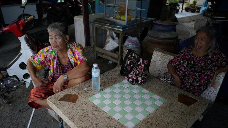 Somjit Teeraroj (L), 77, and Poonsri Seangnual (R), spend time with each other at a shop. After the death of her husband of 40 years, and her children visiting occasionally, Somjit said it was the school that helped her recover from her loss. Her story is emblematic of a larger problem in Thailand --a rapidly ageing population. (Athit Perawongmetha / REUTERS)