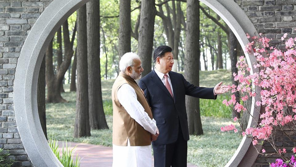"A file photo of PM Modi and Chinese President  Jinping at a garden in Wuhan, China from April. ""India and China should resume military exchanges and strategic communication between top commanders to maintain peace and tranquillity in the border areas,"" India's envoy to China Gautam Bambawale said on Wednesday. (AP File)"