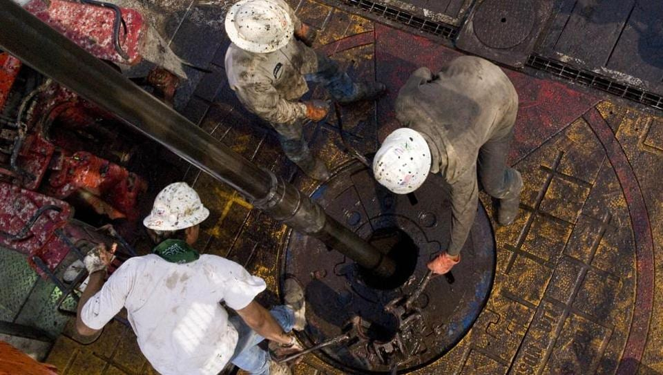 Patterson UTI Drilling Co. floorhands move a drill pipe collar as pipe is removed from a natural gas well being drilled in the Eagle Ford shale in Karnes County, Texas.
