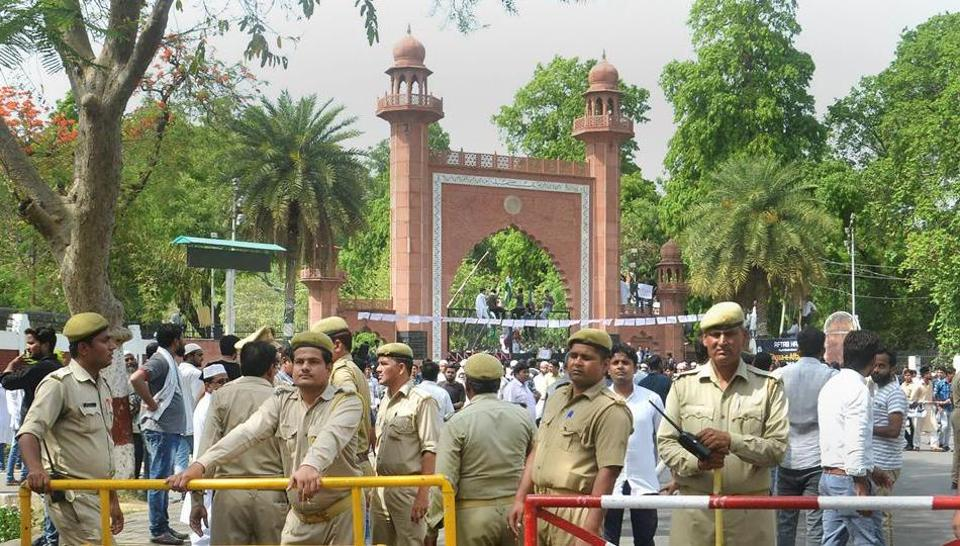 Security personnel stand guard as Aligarh Muslim University students stage a protest over Jinnah portrait issue outside the university gate in Aligarh.