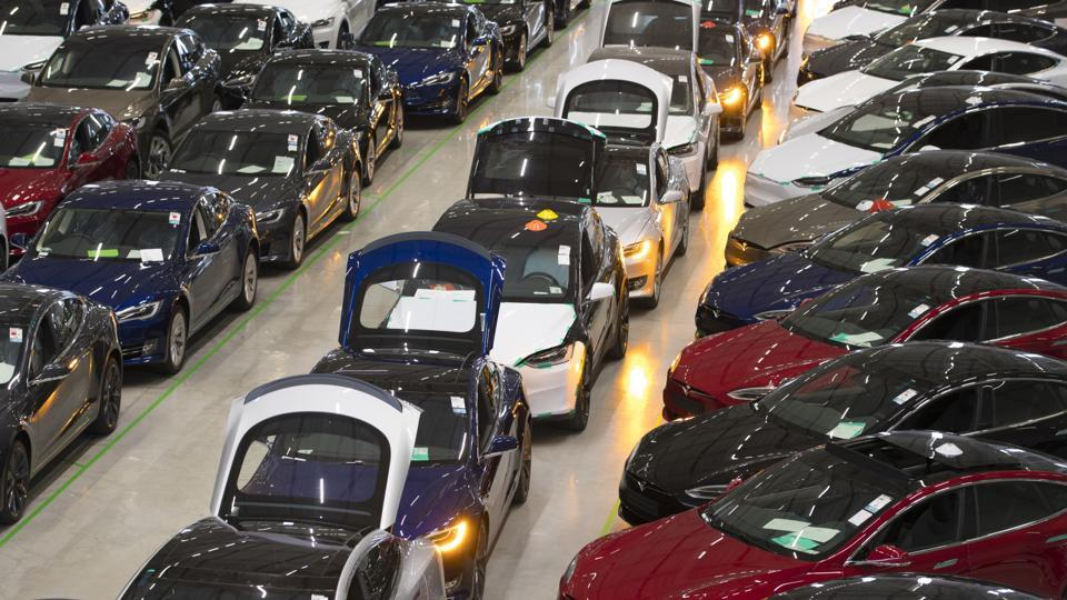 A line of new Tesla Model X sports utility vehicles (SUV), centre, sit with Tesla Model S automobiles following assembly for the European market at the Tesla Motors Inc. factory in Tilburg, Netherlands.