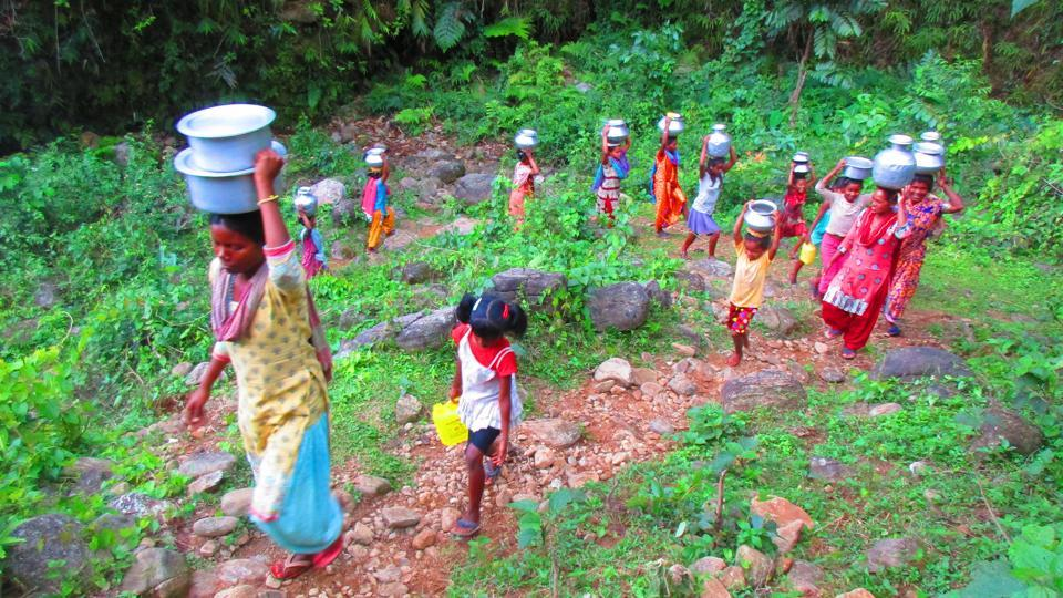 Residents of Carron tea estate in Bengal's Jalpaiguri district bring water from a well in Nainital gewog in Samtse district of Bhutan.
