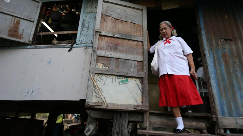 "Poonsri Seangnual, 63, leaves her house wearing her school uniform. ""I really like going to school. I gained knowledge and it's really fun. I have a lot of friends, know a lot more people,"" said Seangnual. ""I feel lonely whenever I don't go to school, I want to go back and meet my friends. I miss the classroom."" (Athit Perawongmetha / REUTERS)"