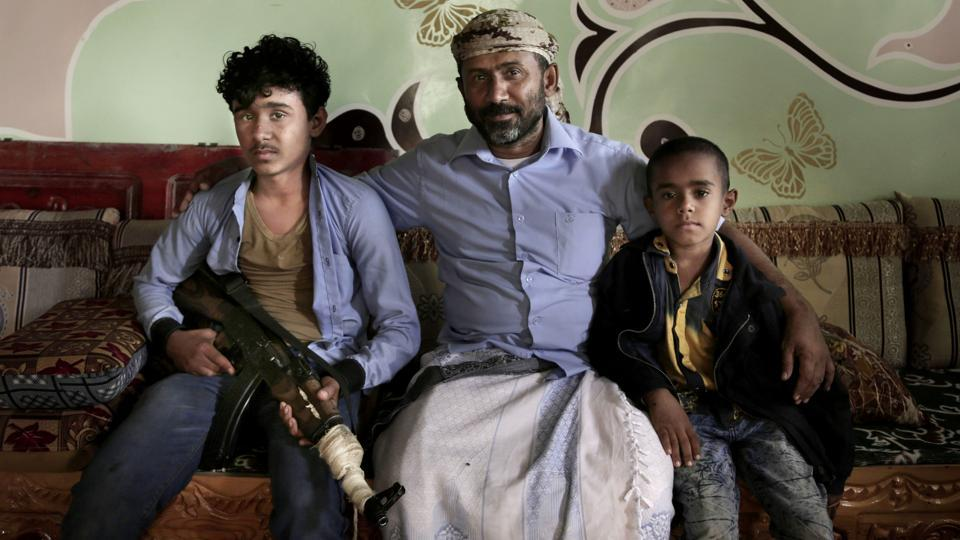 Ahmed al-Kawkabani (C), leader of the southern resistance unit in Hodeida with his 16-year-old son Shaeeb (L) and his 8-year-old Abdullah, at their home. He said his son wants to join him and fight the war. Despite his advise to concentrate more on his studies, Shaeeb finishes school, changes from his uniform and takes up a rifle. (Nariman El-Mofty / AP)