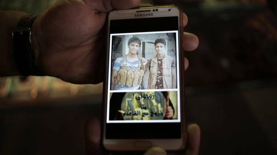 "A photo displayed on the phone of 18-year-old Ahmed Saleh (L) with his friend reads, ""marry me or I will go with Al Qaida."" For Ahmed, Saleh and their friends, it wasn't a fight for President Hadi, it was for the south against the north. Southern Yemen was once independent and separatist sentiment remains powerful. (Nariman El-Mofty / AP)"