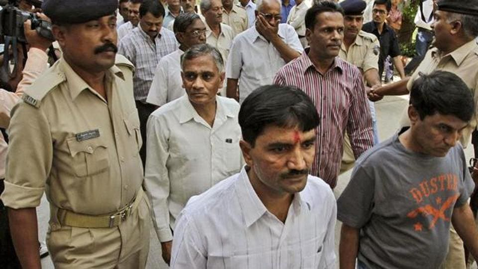 Policemen escort men charged for involvement in the 2002 riots at Ode village into the district court in Anand, Gujarat.