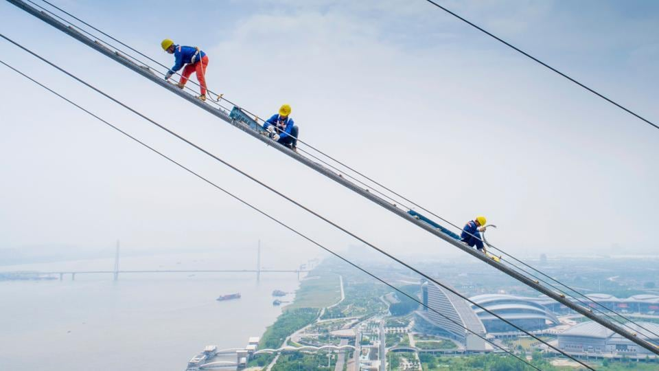 Workers labour on the construction of a double-deck suspension bridge crossing the Yangtze River in Wuhan in China's central Hubei province. (AFP Photo)