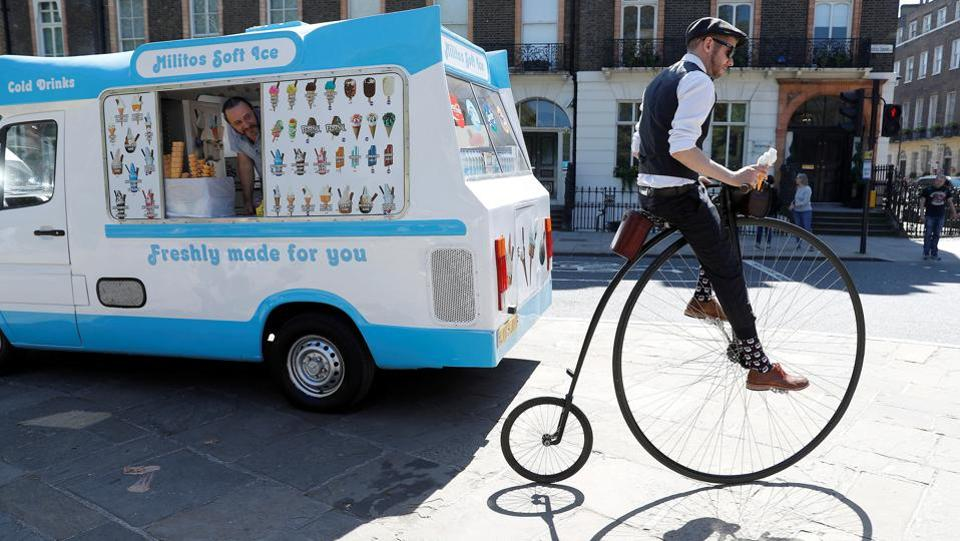 A participant in the Tweed Run cycle ride pulls away from an ice cream van in London, England. (Peter Nicholls / REUTERS)