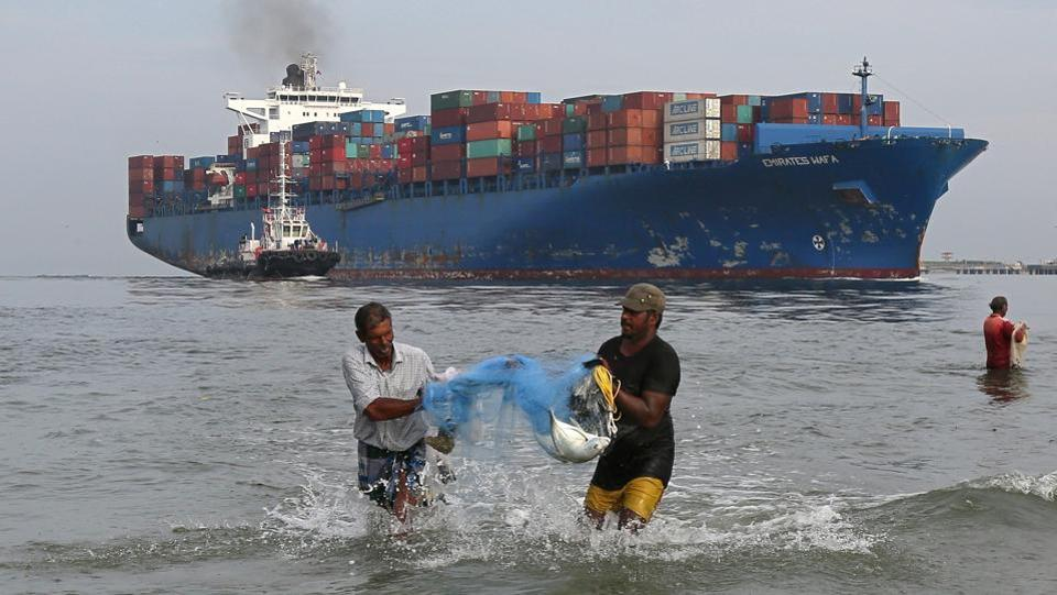 Fishermen carry bluefin trevally fish locally known as Vatta, as a cargo ship carrying containers moves in the Arabian Sea in Kochi on May 09, 2018. (Sivaram V / REUTERS)