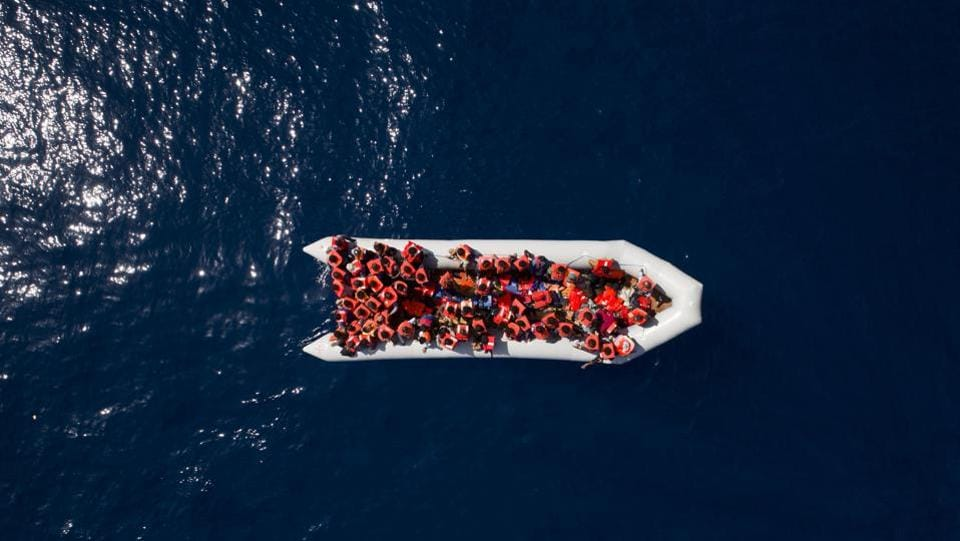 Refugees and migrants wait to be rescued by members of the Spanish NGO Proactiva Open Arms, after leaving Libya trying to reach European soil aboard an overcrowded rubber boat, north of the Libyan coast. (Felipe Dana / AP)